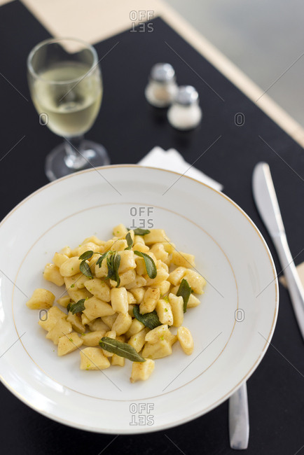 Plate of gnochetti in a sage butter sauce served with a glass of white wine