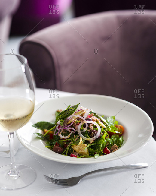 Artichoke salad with basil, red onions and tomatoes served with a glass of white wine