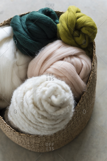 Different colored balls of wool in a basket
