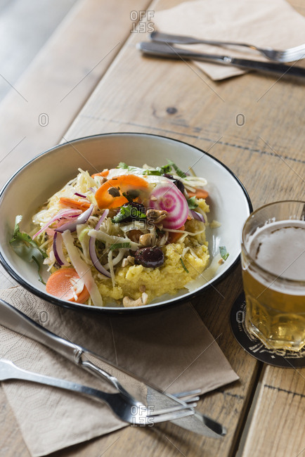 Dish of salad served with polenta served with glass of beer on wooden table