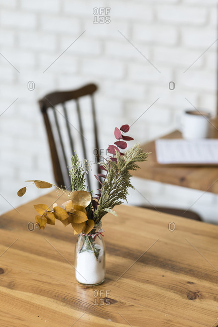 A small arrangement of dried herbs and leaves on a table in a restaurant