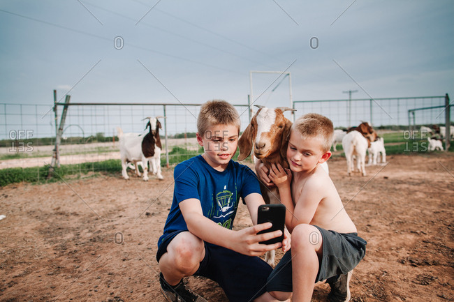 Two boys taking a selfie with goats