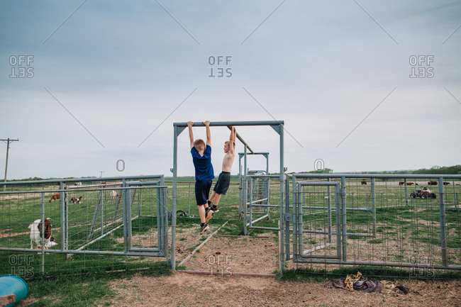 Two boys hanging on a gate