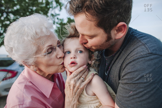 An older lady and man kissing a toddler