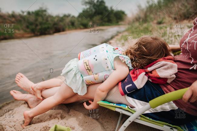 A girl laying on her mother's legs on a beach