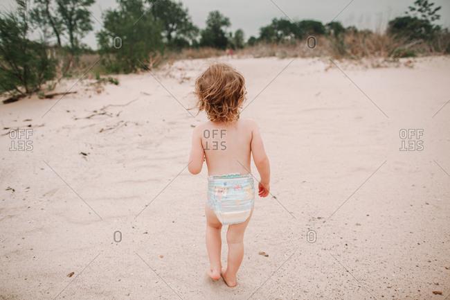 A little girl playing on a sandy beach