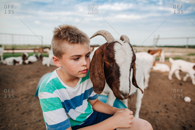 A boy sitting with his pet goat
