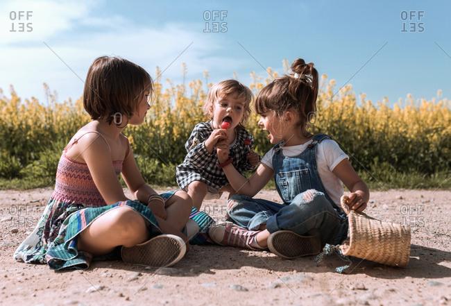 Three girls share a lollipop