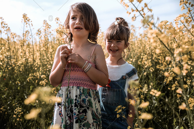Two girls are standing on countryside with flowers