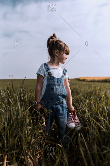 A girl stands inn the countryside while holding a pair of sneakers