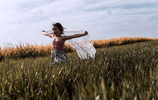 A little girl with a dress plays with veil in the countryside