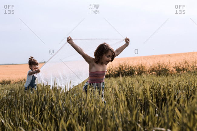 Two girls are playing with a veil in the countryside