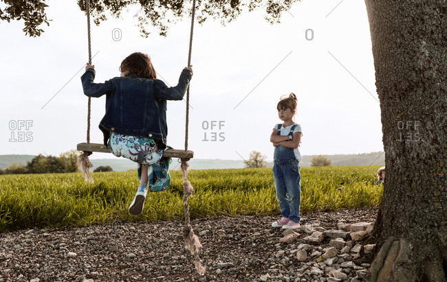 A little girl plays on a swing while her sister waits to play