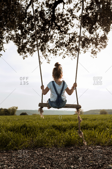 Rear view of a little blonde girl playing with a swing in sunset