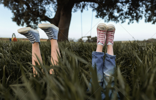 Two little girls are hide in the grass with raised feet