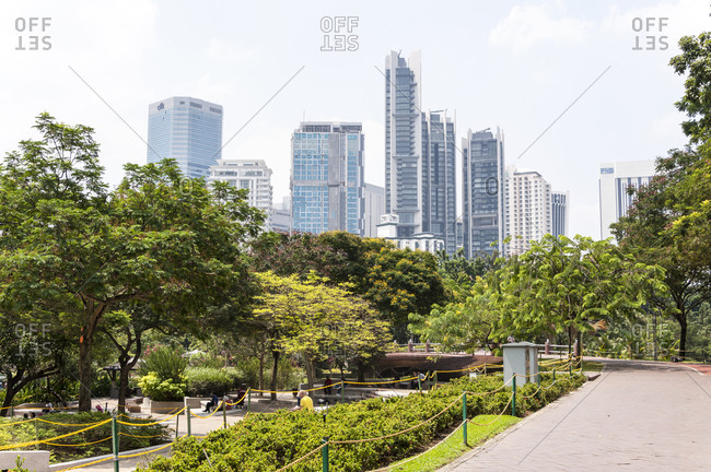 Kuala Lumpur, Malaysia - May 22, 2012: Sunny garden park in front of skyscrapers