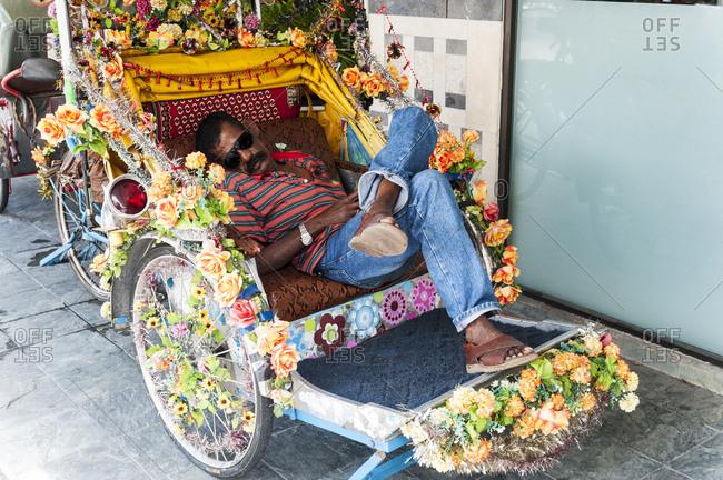 Penang, Malaysia - June 28, 2012: Rickshaw driver taking a nap