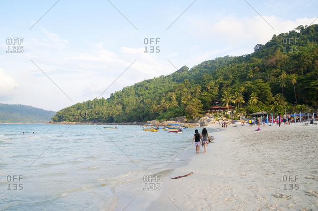 Women enjoying walk on sunny shoreline of Long Beach, Malaysia