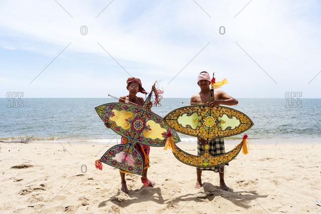 Khota Bharu, Malaysia - July 10, 2012: Two kite flyers posing on sunny beach in Malaysia
