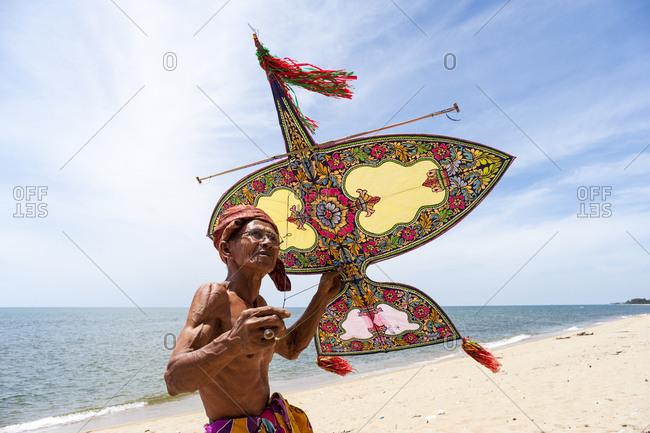 Khota Bharu, Malaysia - July 10, 2012: Man holding kite on Malaysian beach