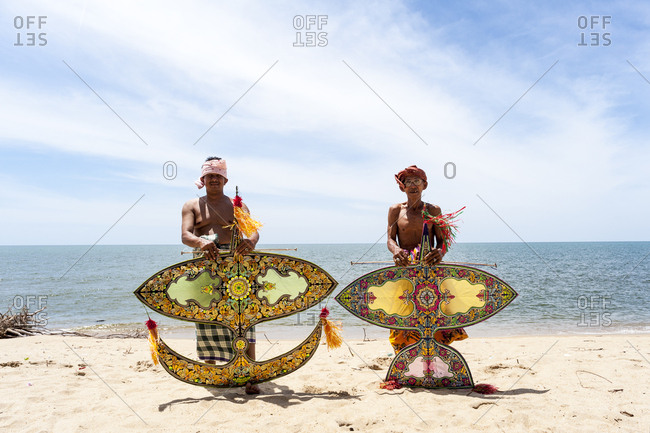 Khota Bharu, Malaysia - July 10, 2012: Two shirtless men holding kites on beach