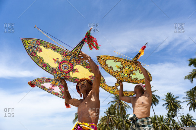 Khota Bharu, Malaysia - July 10, 2012: Low angle view of two men preparing to fly kites