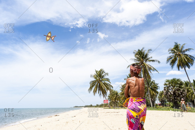Khota Bharu, Malaysia - July 10, 2012: Back view of man guiding kite high on sky on beach