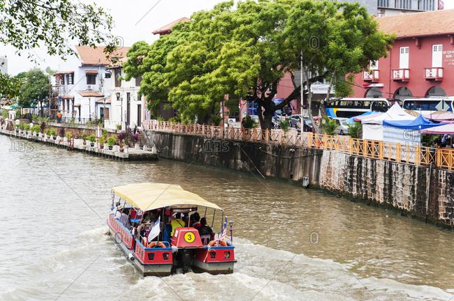 Melaka, Malaysia - July 14, 2012: Small boat cruise in city canal