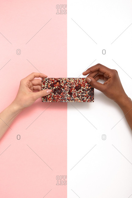Hands of unrecognizable women with different skin color holding smartphone in shining case against white and pink background