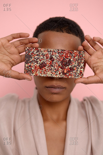 Conceptual portrait of young Black woman with short haircut hiding her eyes with smartphone in glittery case on pink background