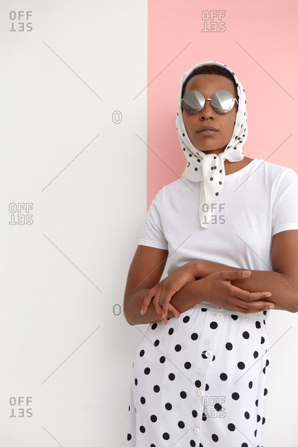 Portrait of African American woman in elegant summer outfit posing on camera while standing against white and pink background