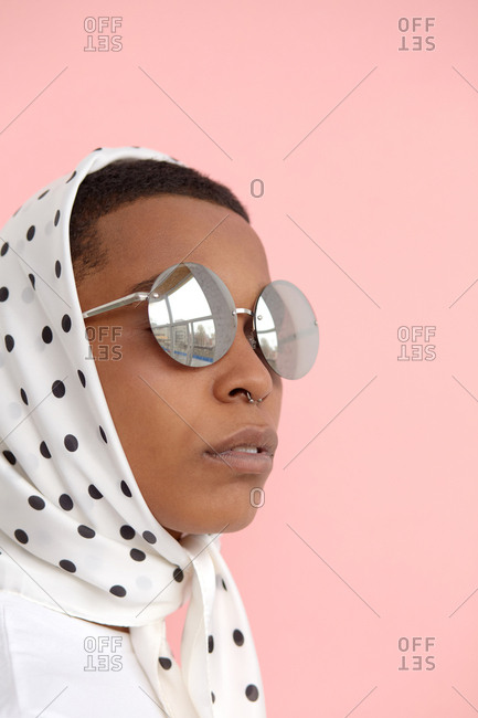 Headshot of stylish Black woman with nose piercing in black and white polka dot headscarf and round sunglasses posing on camera
