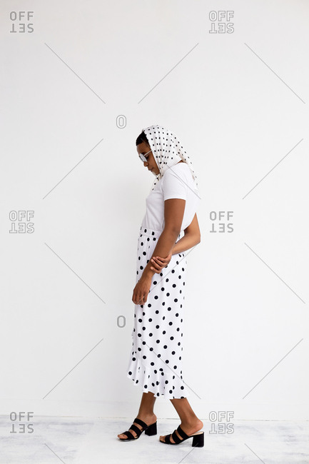 Full-length portrait of fashionable African American woman in black and white polka dot skirt and headscarf posing against white wall, side view