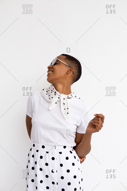 Portrait of stylish African American woman with short haircut in polka dot skirt and scarf posing against white background