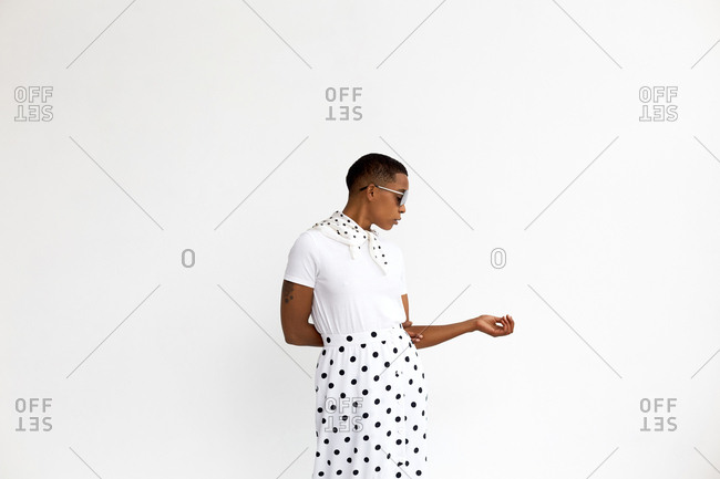 Portrait of androgynous African American woman in stylish polka dot skirt and sunglasses posing against white background