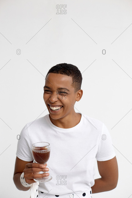 Portrait of androgynous Black woman in white t-shirt holding glass of red wine and smiling cheerfully against white wall background