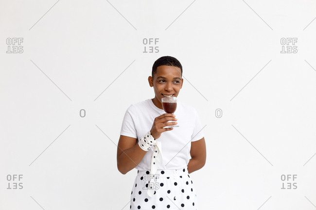 Portrait of stylish manlike African American woman with short afro haircut sipping red wine from glass and smiling happily on white background