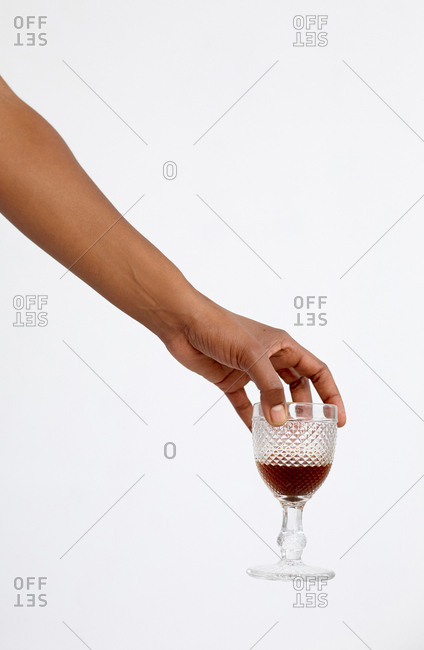 Hand of anonymous Black woman holding glass of alcoholic drink against white background