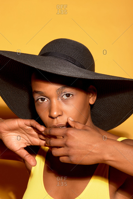 Portrait of androgynous Black woman in swimsuit and wide brimmed sun hat looking at camera with serious face expression on orange background