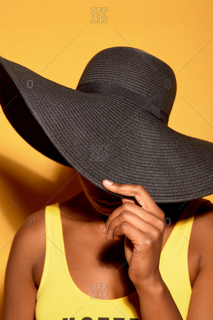 Portrait of anonymous tanned woman in swimsuit hiding her face with wide brimmed sun hat against orange background