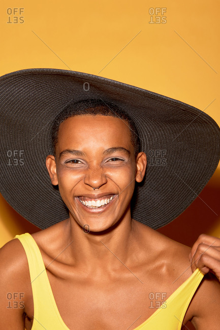 Portrait of androgynous African woman in wide brimmed sun hat smiling at camera cheerfully against orange background