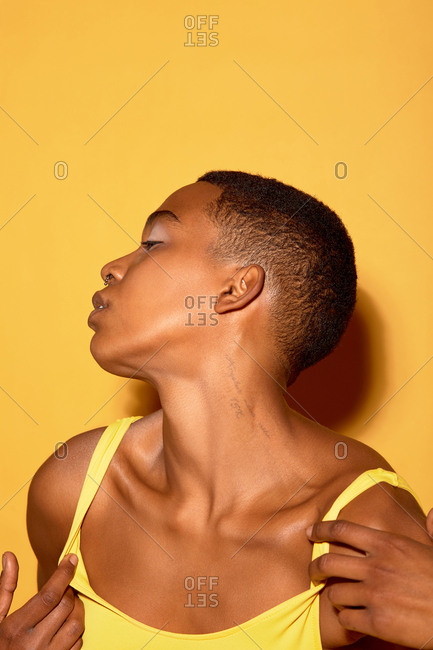 Portrait of sensual Black woman with short haircut and pierced nose posing in seductive way against orange background