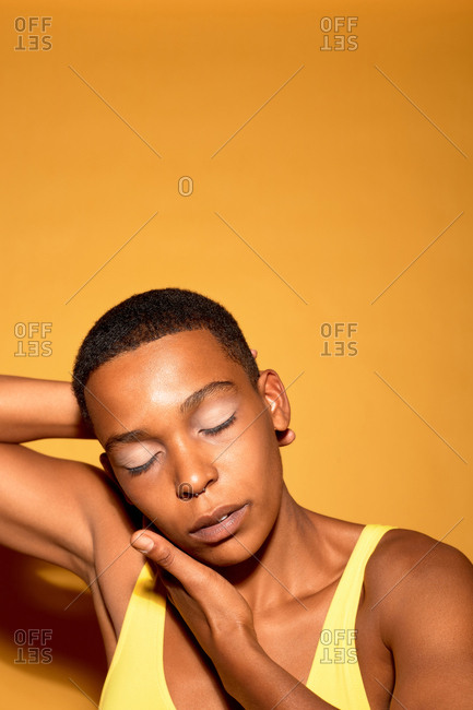 Portrait of attractive muscular Black woman in swimsuit posing with her eyes closed against orange background, copy space