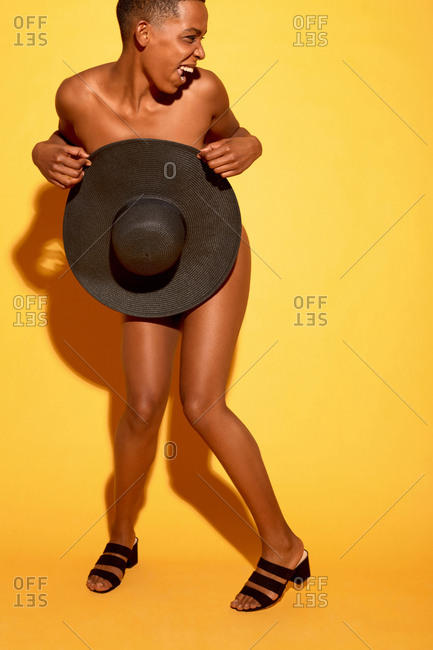 Full-length portrait of naughty Black woman covering her naked body with sun hat, dancing and laughing against orange background