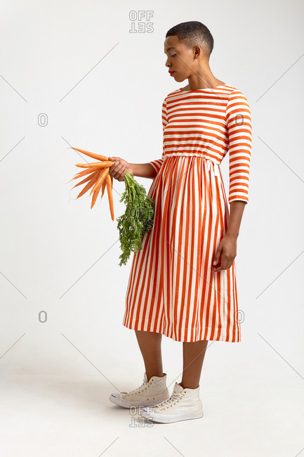 Full-length portrait of attractive Black woman with short haircut in elegant striped dress holding fresh carrots on white background