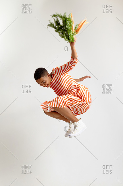 Portrait of African American woman in stylish striped dress jumping high with carrots and smiling happily on white background