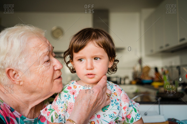 Grandmother leaning in to kiss granddaughter's cheek