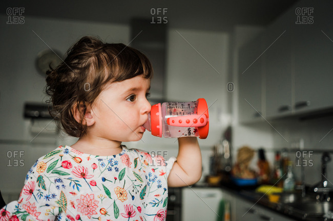Toddler girl drinking water at home