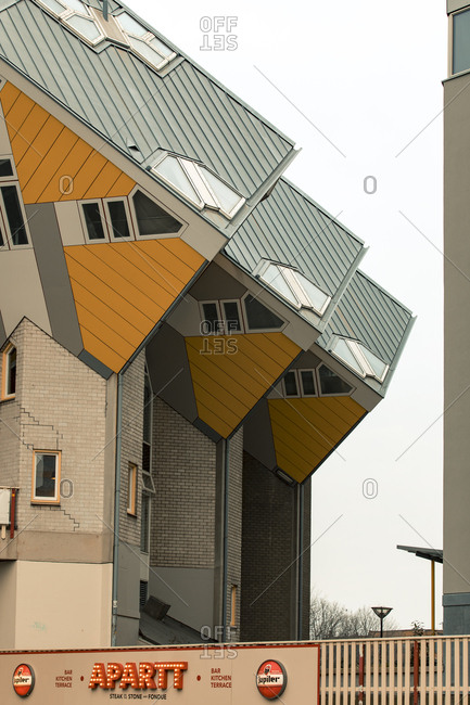 Rotterdam, Netherlands - June 07, 2018: Architect Piet Blom's angled cubic houses on pillars overlooking a restaurant on Blaak Street