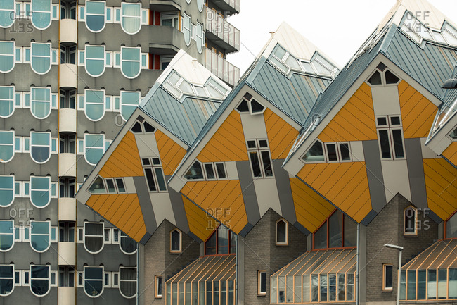 Rotterdam, Netherlands - June 07, 2018: A small forest of cube houses by architect Piet Blom and a neighboring apartment building in the background